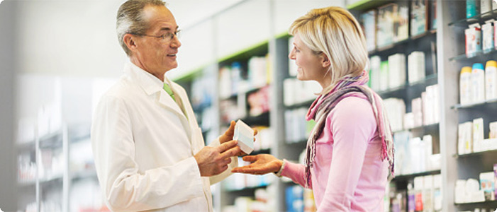A pharmacist handing a box of medicine to a customer and giving her advice.