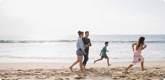 A man and wife and their two children running along the beach.