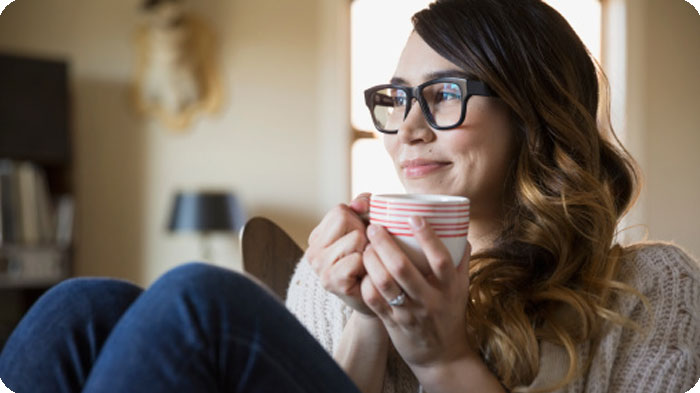 Woman with glasses drinking a cup of tea and watching television.
